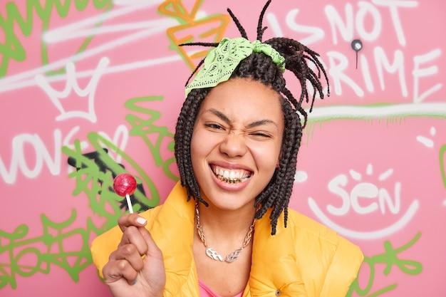 Stylowa nastolatka zaciska zęby, bawi się z przyjaciółmi w pozach na tle ściany graffiti trzyma lollipop ma modną fryzurę nosi metalowy łańcuszek na szyi żółta kamizelka