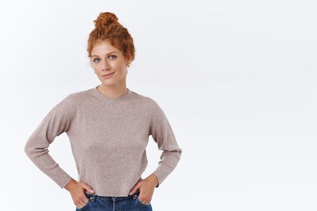 Stylowa, nowoczesna kobieta rasy kaukaskiej z rudymi kręconymi włosami zaczesanymi w kok, trzymaj ręce w kieszeniach dżinsów, patrząc z przodu ze szczęśliwym, zadowolonym uśmiechem, noś elegancki sweter, koncepcję biznesową i przedsiębiorczą