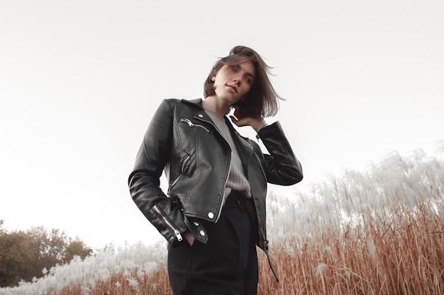Stylowa nowoczesna kobieta w czarnej skórzanej kurtce pozuje wśród puszystej trawy.