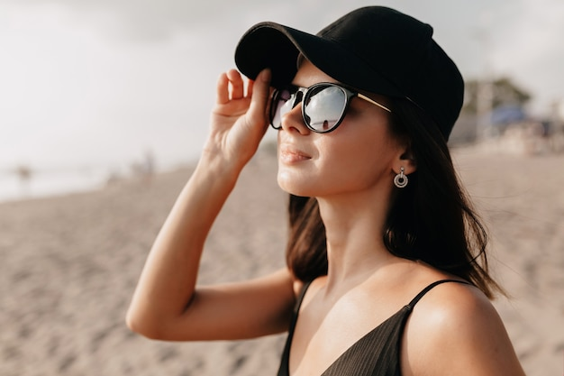 Stylowa, nowoczesna kobieta w modnym stroju, patrząc na ocean ze szczęśliwym uśmiechem w czapce i okularach i cieszy się letnimi upalnymi dniami młoda kaukaska modelka na brzegu morza