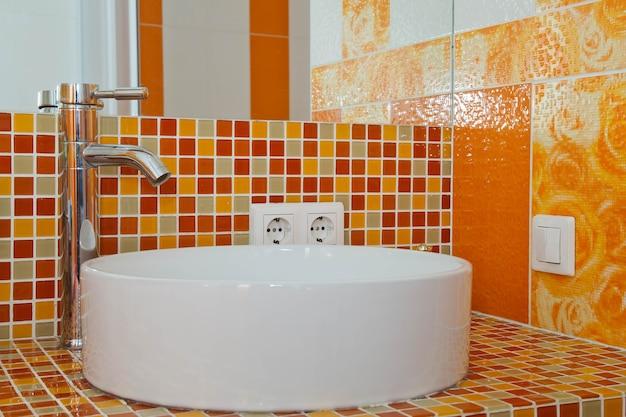 Stylowa nowoczesna umywalka we wnętrzu z pomarańczowymi płytkami dekoracyjnymi w łazience