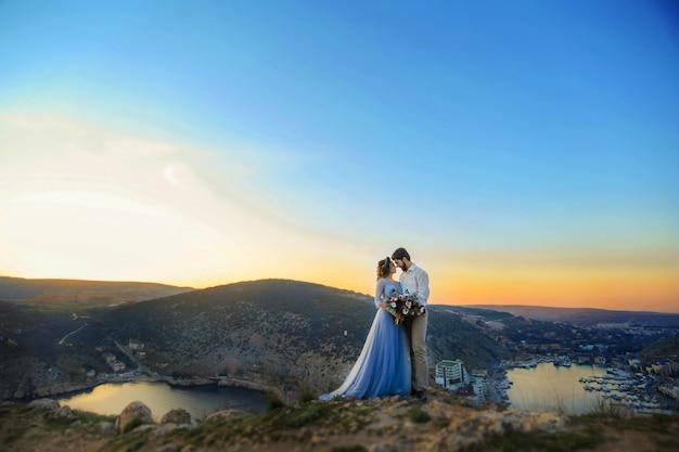 Stylowa nowożeńcy przytulają się w naturze, na tle skał i skał.