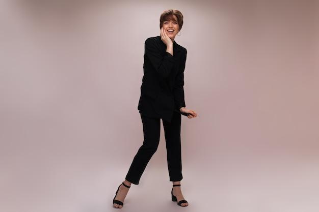 Stylowa pani w garniturze, śmiejąc się na na białym tle. pełnowymiarowy portret kobiety ubranej w czarną kurtkę i spodnie, pozowanie i uśmiechając się na białym tle