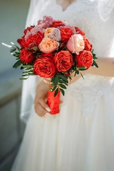 Stylowa panna młoda w białej sukni posiada jasne zbliżenie bukiet ślubny. ślubny bukiet czerwonych kwiatów w rękach młodej.