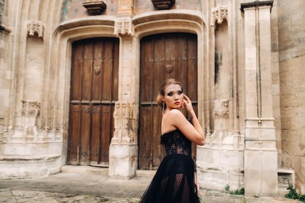 Stylowa panna młoda w czarnej sukni ślubnej pozuje w starożytnym francuskim mieście awinion. modelka w pięknej czarnej sukience. sesja zdjęciowa w prowansji.