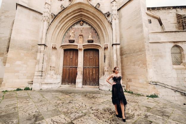 Stylowa panna młoda w czarnej sukni ślubnej pozuje w starożytnym francuskim mieście awinion