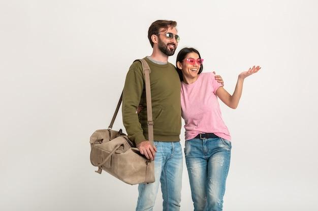 Stylowa para na białym tle, dość uśmiechnięta kobieta w różowej koszulce i mężczyzna w bluzie trzymający torbę podróżną, ubrany w dżinsy, w okularach przeciwsłonecznych, wspólna zabawa, wskazujący palec