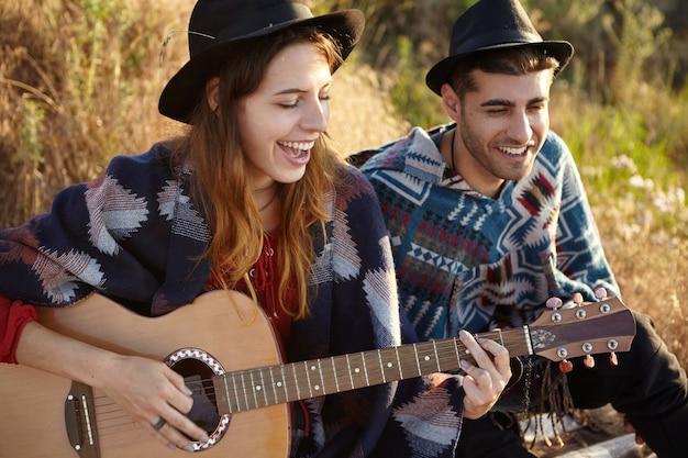Stylowa para z gitarą na polu