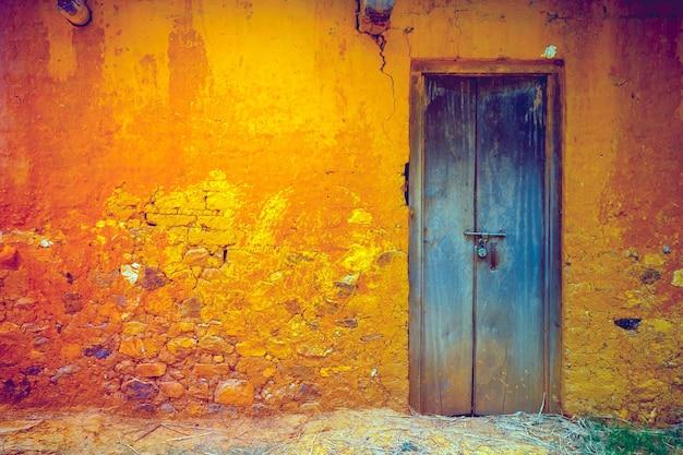 Stylowa pęknięta kolorowa ściana w stylu vintage w żółto-pomarańczowych odcieniach z idealnymi drewnianymi drzwiami w kolorze królewskim niebieskim