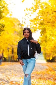 Stylowa piękna czarna dziewczyna w modnych ubraniach z casualową marynarką i niebieskimi dżinsami z torebką spaceruje po jesiennym parku z kolorowymi złotymi jesiennymi liśćmi