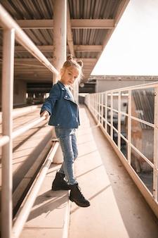 Stylowa, piękna dziewczyna około siedmiu lat w dżinsowej kurtce spaceruje po ulicy