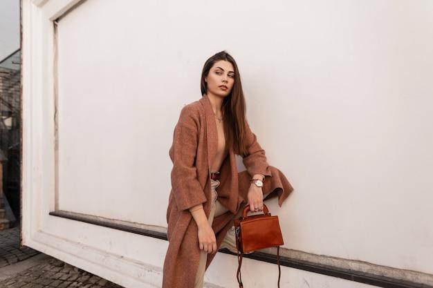 Stylowa piękna dziewczyna w modnej odzieży wierzchniej stoi pod ścianą