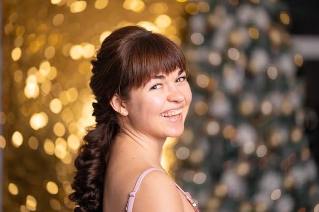 Stylowa piękna dziewczyna wśród błyskotek i gerlands na przyjęciu bożonarodzeniowym.