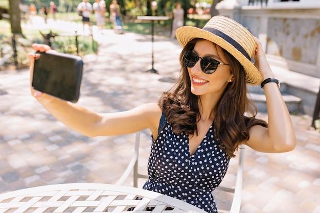 Stylowa piękna kobieta o krótkich ciemnych włosach i czarującym uśmiechu siedzi w letniej kawiarni w słońcu. ma na sobie letni kapelusz i okulary przeciwsłoneczne i robi selfie.
