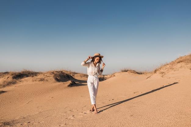 Stylowa piękna kobieta spaceru w piasku pustyni w białym stroju na sobie słomkowy kapelusz na zachód słońca