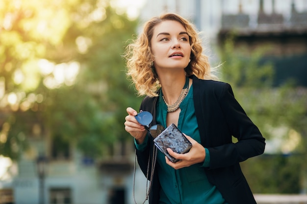 Stylowa piękna kobieta w dżinsach i kurtce spacerująca po ulicy z małą torebką, elegancki styl, wiosenne trendy w modzie