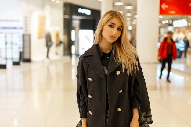 Stylowa piękna kobieta w modny jesienny płaszcz pozowanie w centrum handlowym