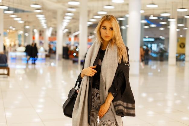 Stylowa piękna kobieta w modnych jesiennych ubraniach w centrum handlowym