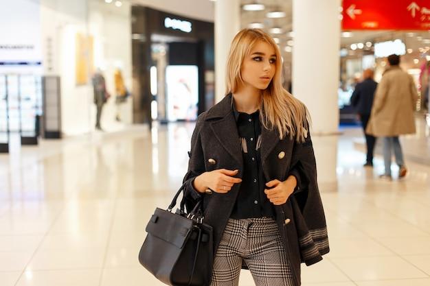Stylowa piękna kobieta w modnym płaszczu z torebką na zakupy w centrum handlowym