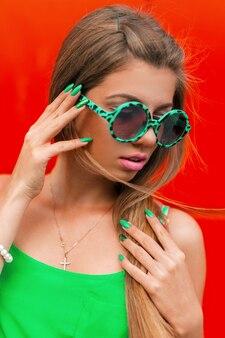 Stylowa piękna kobieta w okrągłych okularach przeciwsłonecznych na jaskrawej czerwieni.