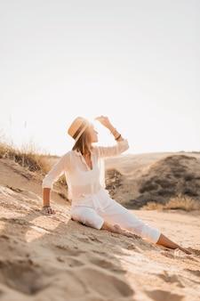 Stylowa piękna kobieta w piasku pustyni w białym stroju na sobie słomkowy kapelusz na zachód słońca