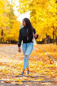 Stylowa piękna młoda afroamerykanka w modnych ubraniach z czarną kurtką i niebieskimi dżinsami z torebką spaceruje po jesiennym parku z kolorowymi żółtymi jesiennymi liśćmi