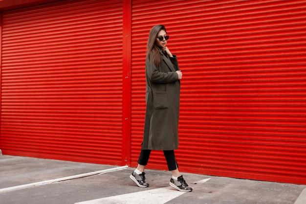Stylowa piękna młoda atrakcyjna kobieta z okulary w modnym płaszczu na czerwonej ścianie spaceru po ulicy. moda uliczna