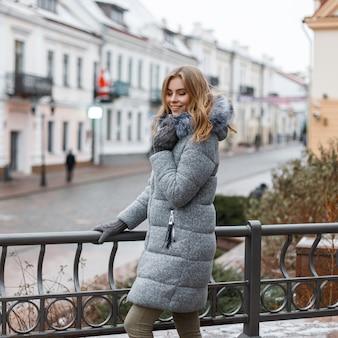 Stylowa piękna młoda kobieta w ciepłej, zimowej modnej odzieży wierzchniej stoi na ulicy w pobliżu żelaznego czarnego ogrodzenia. urocza dziewczyna na wakacjach.