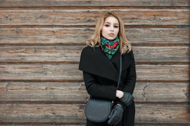 Stylowa piękna młoda kobieta w czarnym płaszczu stojąca w pobliżu vintage drewnianej ścianie