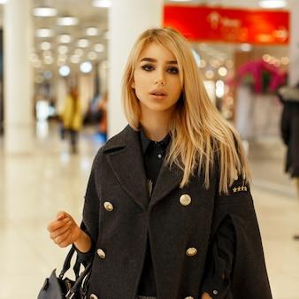 Stylowa piękna młoda kobieta w modnym płaszczu z czarną torebką w centrum handlowym