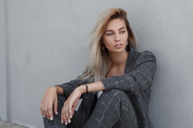 Stylowa piękna młoda modelka w modnym szarym garniturze, siedząc w pobliżu ściany na ulicy