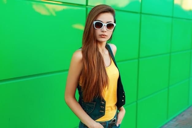 Stylowa piękna modelka w jasnożółtej koszuli i dżinsach pozuje w pobliżu zielonej metalowej ściany.