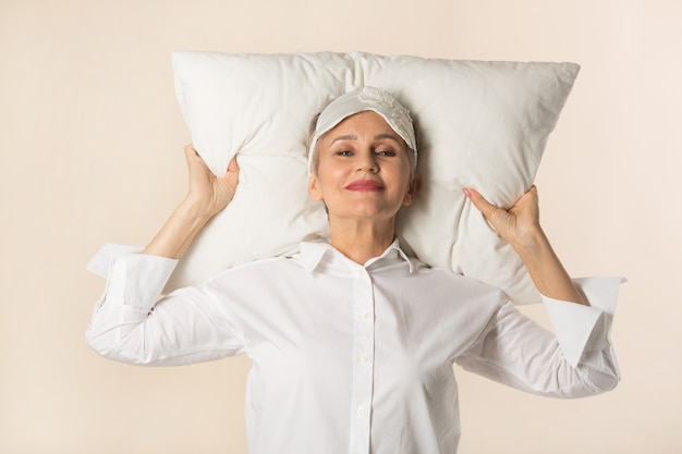 Stylowa piękna starsza kobieta z poduszką w dłoniach