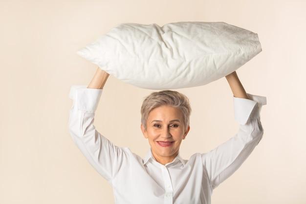 Stylowa piękna starsza kobieta z poduszką w ręce na żółtym tle