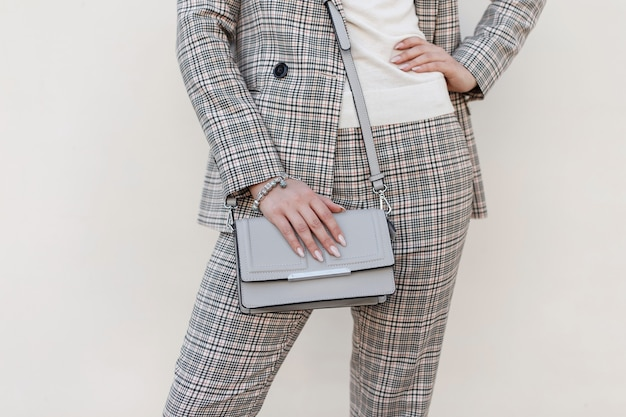 Stylowa piękna torebka damska. młoda dziewczyna w garniturze w kratkę moda z torebką. zbliżenie