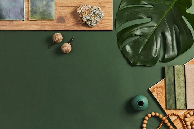 Stylowa, płaska kompozycja kreatywnego projektu moodboard dla architekta z próbkami materiałów budowlanych, tekstylnych i naturalnych oraz osobistych akcesoriów. widok z góry, zielone tło, szablon.