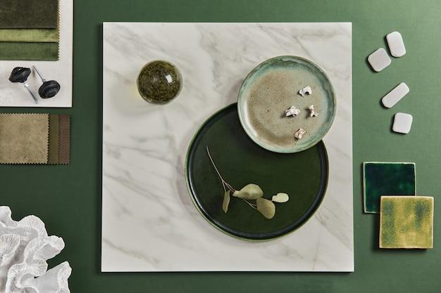 Stylowa, płaska kompozycja kreatywnego projektu moodboard dla architektów z próbkami materiałów budowlanych, tekstylnych i naturalnych oraz osobistych akcesoriów. widok z góry, zielone tło, szablon.