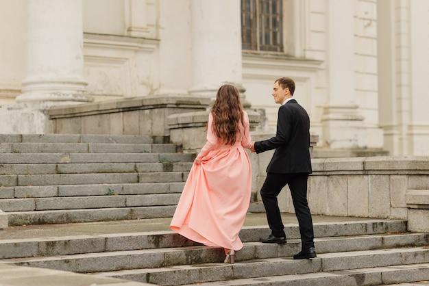 Stylowa po prostu wesoła. para ślub. z bliska. szczęśliwy państwo młodzi chodzi blisko starego kasztelu. ślubny bukiet kwiatów