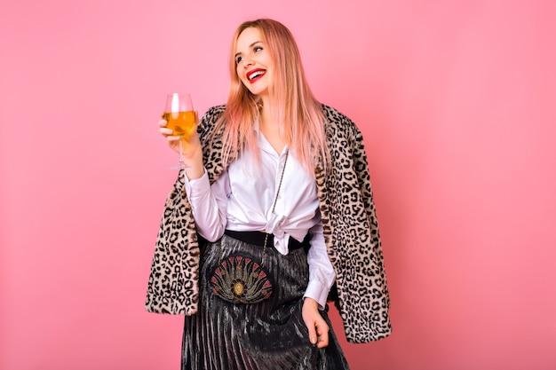 Stylowa, pozytywna ładna młoda kobieta bawiąca się, ubrana w wieczorowy musujący koktajlowy strój i modny płaszcz z nadrukiem w panterkę, różowe tło, ciesząca się imprezą ferii zimowych.