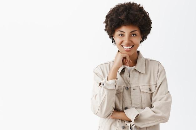 Stylowa, przystojna ciemnoskóra feministka w beżowej koszuli z fryzurą afro trzymająca się za brodę i szeroko uśmiechnięta, zadowolona z tego, dokąd prowadzi rozmowa
