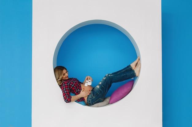 Stylowa przyszła kobieta-matka czule obejmuje i gładzi brzuch. kobieta w ciąży trzyma buty dla noworodka. blond kobieta w oczekiwaniu na poród dziecka.