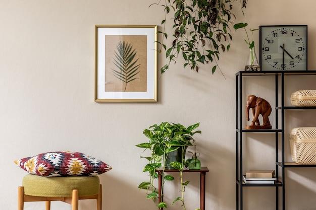 Stylowa retro home inscenizacja salonu ze złotą ramą, designerskimi meblami, mnóstwem roślin, zegarem, rattanowymi pudełkami i eleganckimi akcesoriami osobistymi. vintage wystrój domu...