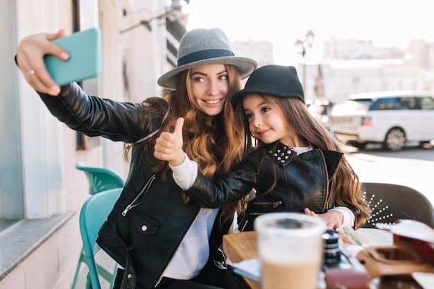 Stylowa rodzina siedząca w miejskiej kawiarni patrzy do telefonu, robi selfie i uśmiecha się na słonecznym tle miasta. mała dziewczynka pokazuje palec do góry patrząc na kamery. prawdziwe emocje, dobry nastrój.