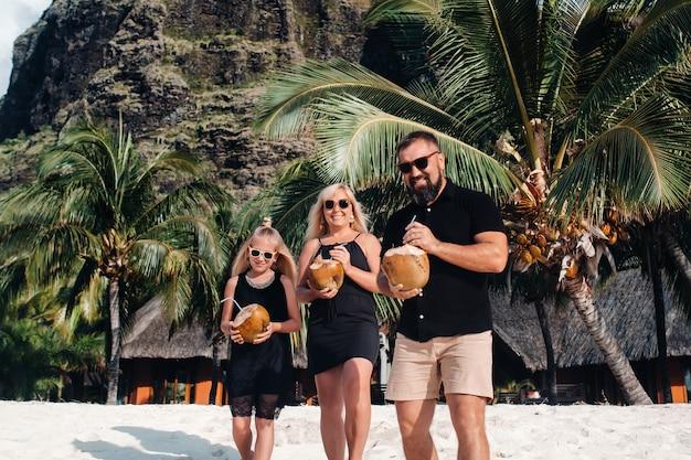 Stylowa rodzina w czarnych ubraniach z kokosami w dłoniach na plaży na wyspie mauritius.piękna rodzina na wyspie mauritius na oceanie indyjskim.