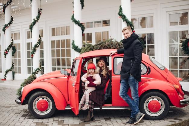 Stylowa rodzina w czerwonym samochodzie na zewnątrz na boże narodzenie