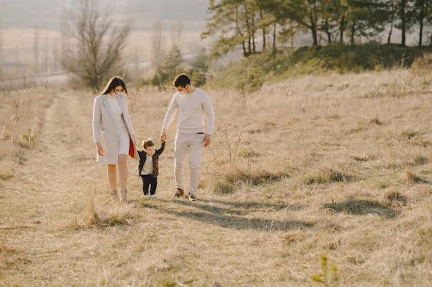 Stylowa rodzina w maskach chodzących na polu wiosny