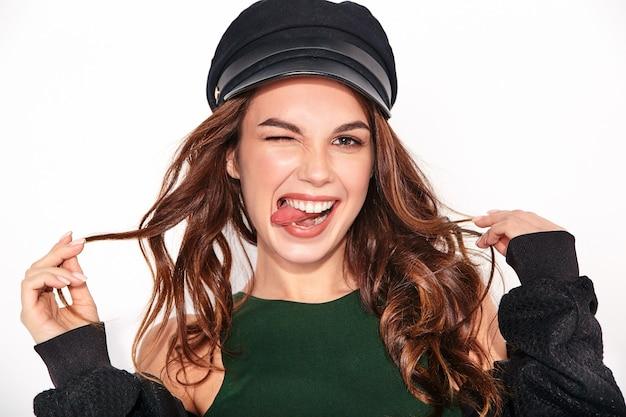 Stylowa roześmiana modelka w czarnych, swobodnych letnich ubraniach w czapce z naturalnym makijażem na białym, dotykająca włosów i pokazująca język