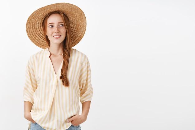 Stylowa rudowłosa kobieta idzie na plażę w słomkowym kapeluszu, aby nie opalać się, skręcając w prawo z radosną beztroską miną, trzymając ręce w kieszeniach, ciesząc się ciepłym słonecznym letnim dniem