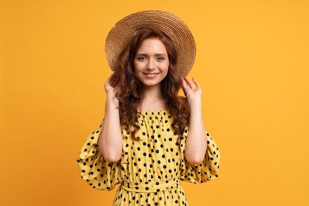 Stylowa rudowłosa kobieta pozuje w żółtej sukience z rękawami na żółto. letni nastrój.