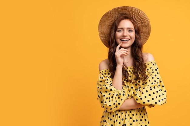 Stylowa rudowłosa kobieta pozuje w żółtej sukience z rękawami na żółto.